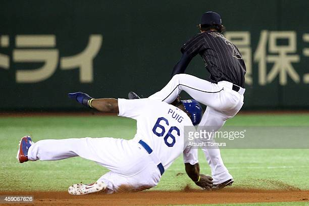 Yasiel Puig of the Los Angeles Dodgers slides into while Kenta Imamiya of Samurai Japan throws to first base to complete the double play in the fifth...