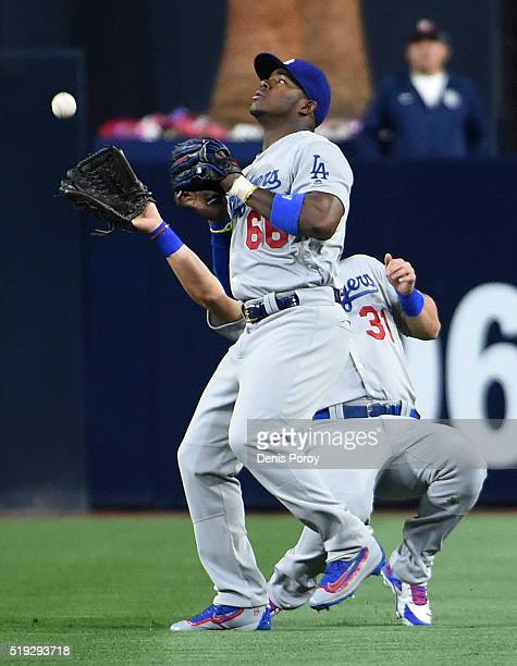 Yasiel Puig of the Los Angeles Dodgers steps in front of Joc Pederson as he makes a catch on a ball hit by Matt Kemp of the San Diego Padres during...