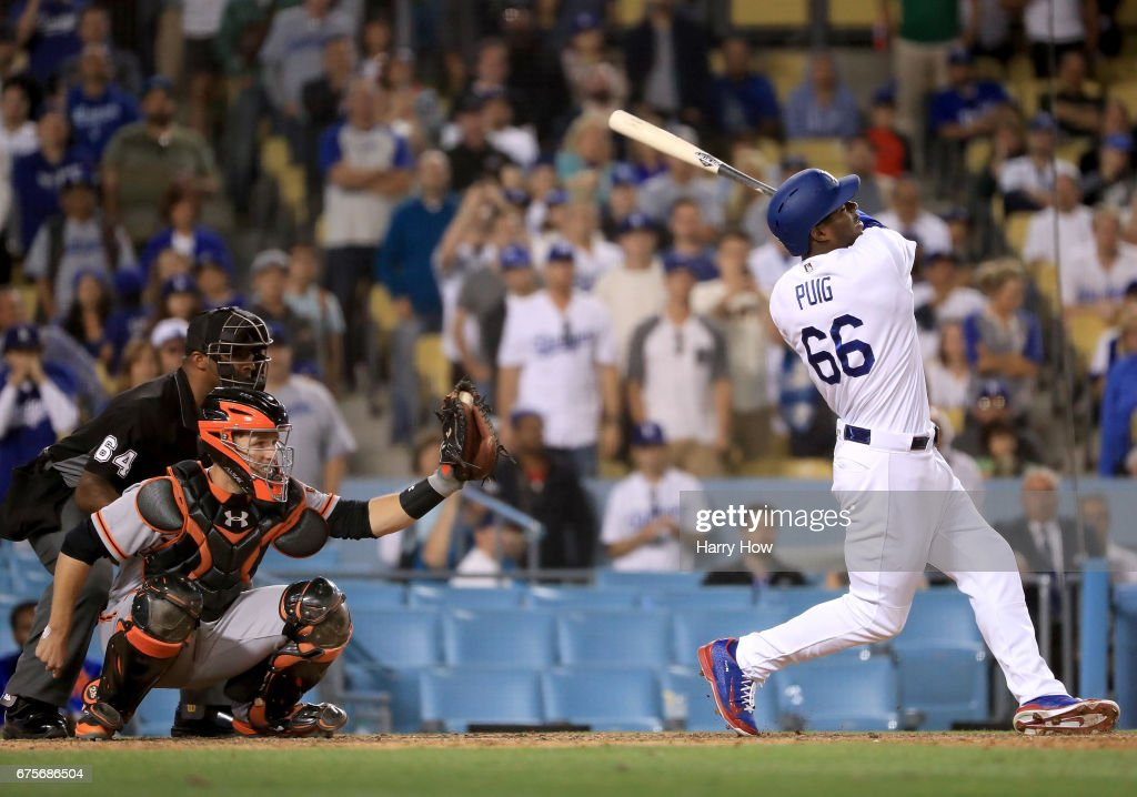 Yasiel Puig #66 of the Los Angeles Dodgers strikes out in front of Buster Posey #28 of the San Francisco Giants to end the game and a 4-3 Giants win at Dodger Stadium on May 1, 2017 in Los Angeles, California.