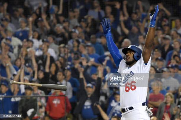 Yasiel Puig of the Los Angeles Dodgers tosses his bat aside and celebrates as his hit goes for a threerun home run to left field in the sixth inning...