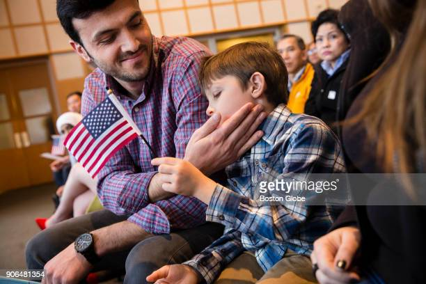 Yasin Akkaya originally from Turkey touches his son Gabriel's cheek after taking the oath of citizenship during a naturalization ceremony at the John...