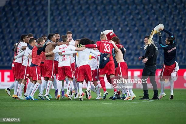 Yasin Pehlivan sprays beer on coach Oscar Garcia meanwhile the team of Red Bull Salzburg celebrates after the tipico Bundesliga match between Red...