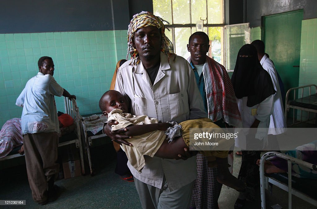 Yasin Sudi carries his son Ayub Yasin, 6, at the Banadir hospital on August 16, 2011 in Mogadishu, Somalia. The hospital has been overwhelmed by new patients, as sickness spreads through camps for people displaced by drought and famine. The US government estimates that some 30,000 children have died in southern Somalia in the last 90 days from the crisis.