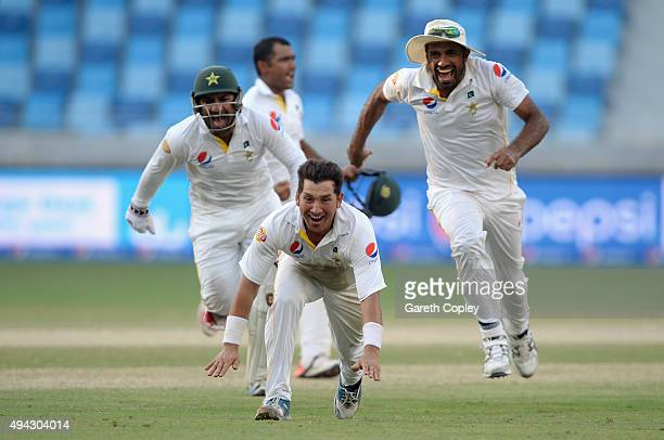 Yasir Shah of Pakistan celebrates with teammates Sarfraz Ahmed and Wahab Riaz after dismissing Adil Rashid of England to win the 2nd test match...