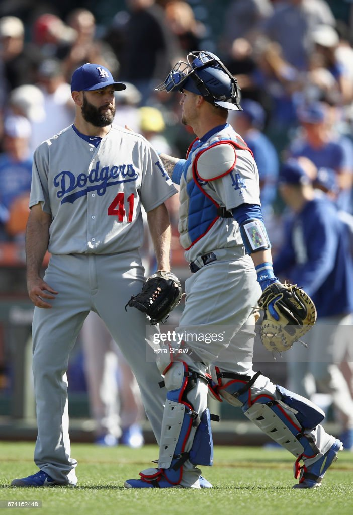 Yasmani Grandal #9 congratulates Chris Hatcher #41 of the Los Angeles Dodgers after they beat the San Francisco Giants in 10 innings at AT&T Park on April 27, 2017 in San Francisco, California.
