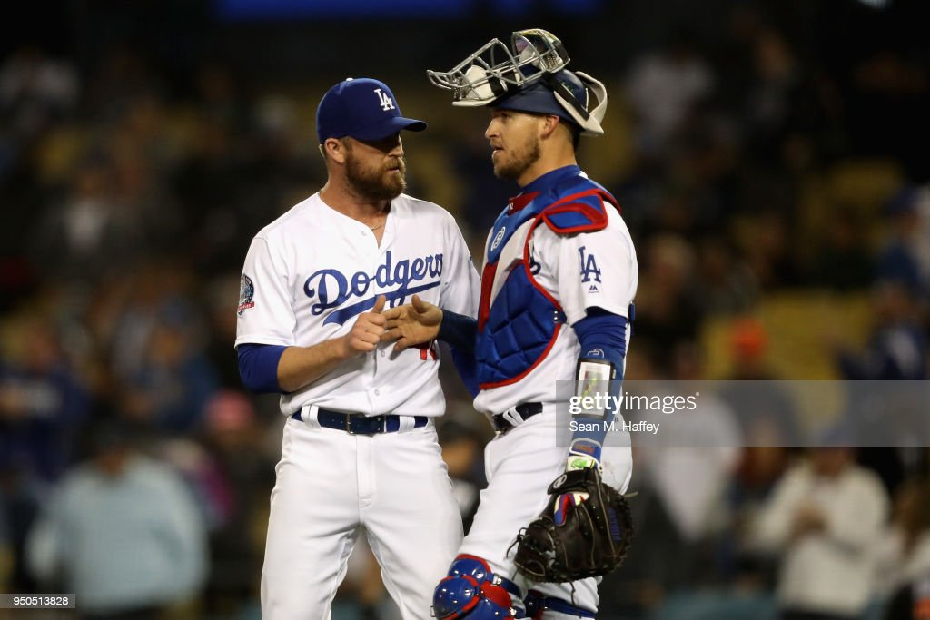 Yasmani Grandal #9 congratulates Josh Fields #46 of the Los Angeles Dodgers after defeating the Miami Marlins 2-1 in a game at Dodger Stadium on April 23, 2018 in Los Angeles, California.