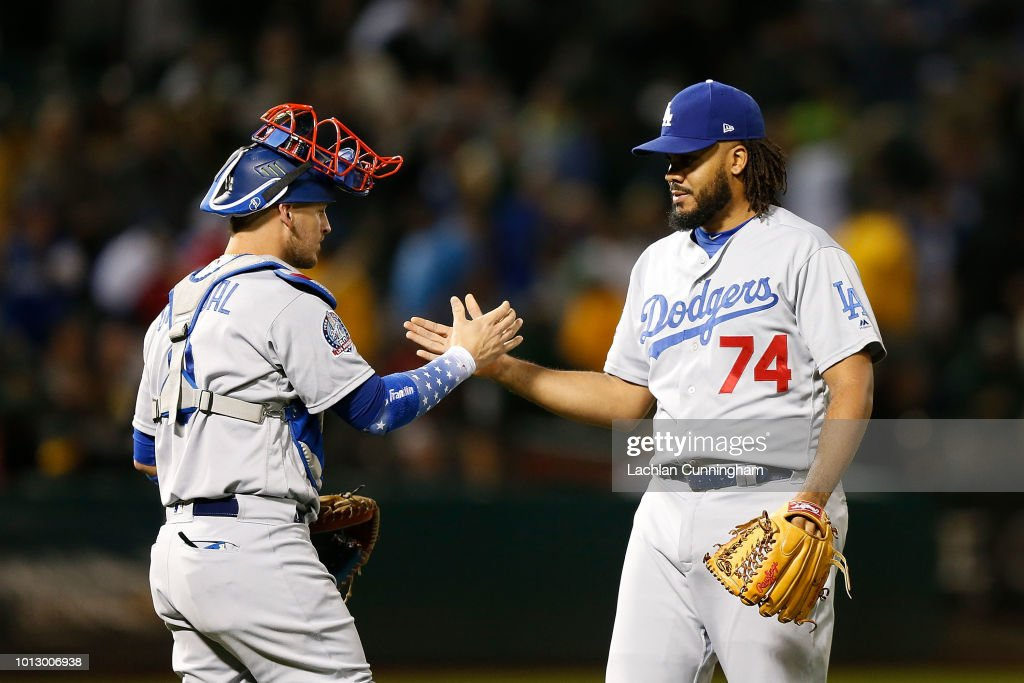 Yasmani Grandal #9 of the Los Angeles Dodgers and Kenley Jansen #74 celebrate after a win against the Oakland Athletics at Oakland Alameda Coliseum on August 7, 2018 in Oakland, California.