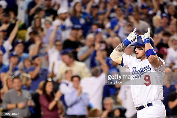 Yasmani Grandal of the Los Angeles Dodgers celebrates aftre he hits a tworun home run in the fourth inning against the Chicago Cubs in game three of...
