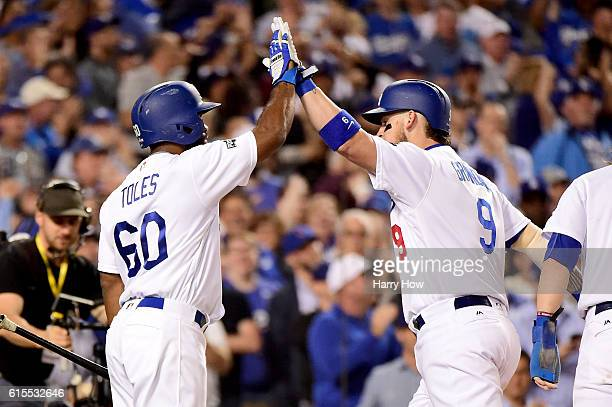 Yasmani Grandal of the Los Angeles Dodgers celebrates with Andrew Toles after Grandal hits a tworun home run in the fourth inning against the Chicago...
