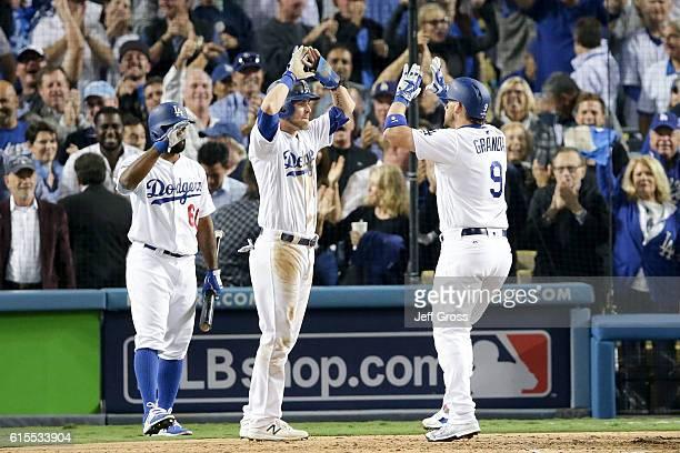 Yasmani Grandal of the Los Angeles Dodgers celebrates with Josh Reddick and Andrew Toles after hitting a tworun home run against the Chicago Cubs in...