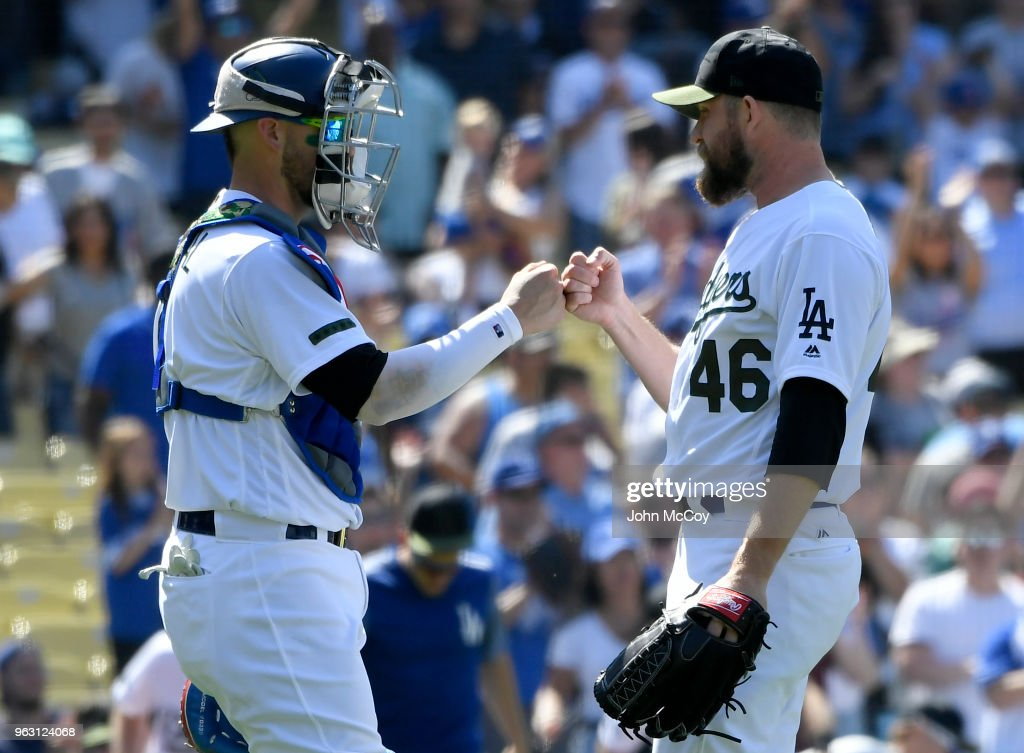 Yasmani Grandal #9 of the Los Angeles Dodgers congratulates Josh Fields #46 after the final out against the San Diego Padres at Dodger Stadium on May 27, 2018 in Los Angeles, California. Dodger won 6-1.