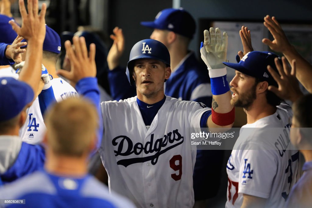 Yasmani Grandal #9 of the Los Angeles Dodgers is congratulated in the dugout during a game against the San Diego Padres at Dodger Stadium on September 26, 2017 in Los Angeles, California.