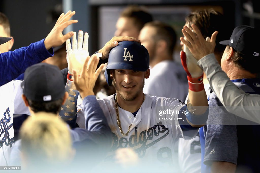 Yasmani Grandal #9 of the Los Angeles Dodgers is congratulated in the dugout after hitting a solo home run during the sixth inning of a game against the Pittsburgh Pirates at Dodger Stadium on July 3, 2018 in Los Angeles, California.