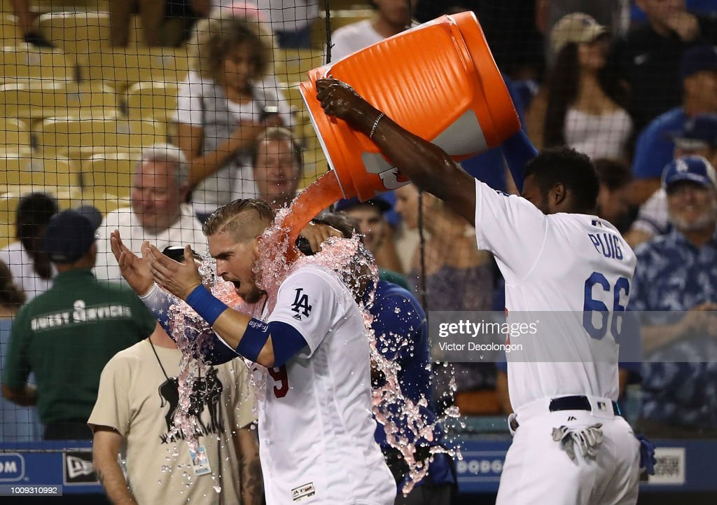 Yasmani Grandal #9 of the Los Angeles Dodgers is doused with Gatorade by teammate Yasiel Puig #66 after Grandal hit a two-run walk-off homerun over the right field fence in the tenth inning of the MLB game against the Milwaukee Brewers at Dodger Stadium on August 1, 2018 in Los Angeles, California. The Dodgers defeated the Brewers 6-4.