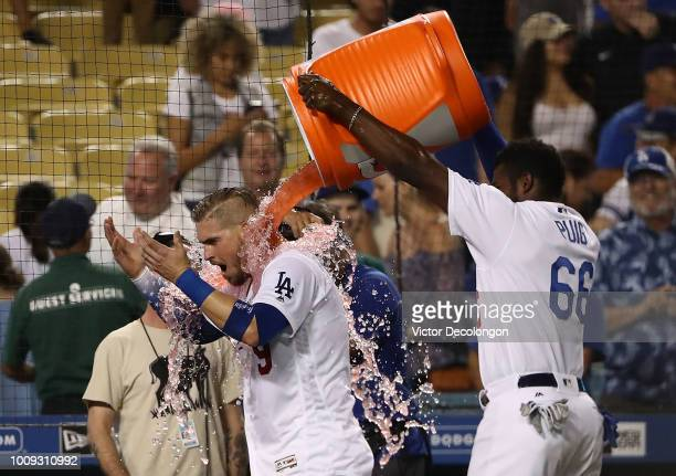Yasmani Grandal of the Los Angeles Dodgers is doused with Gatorade by teammate Yasiel Puig after Grandal hit a tworun walkoff homerun over the right...