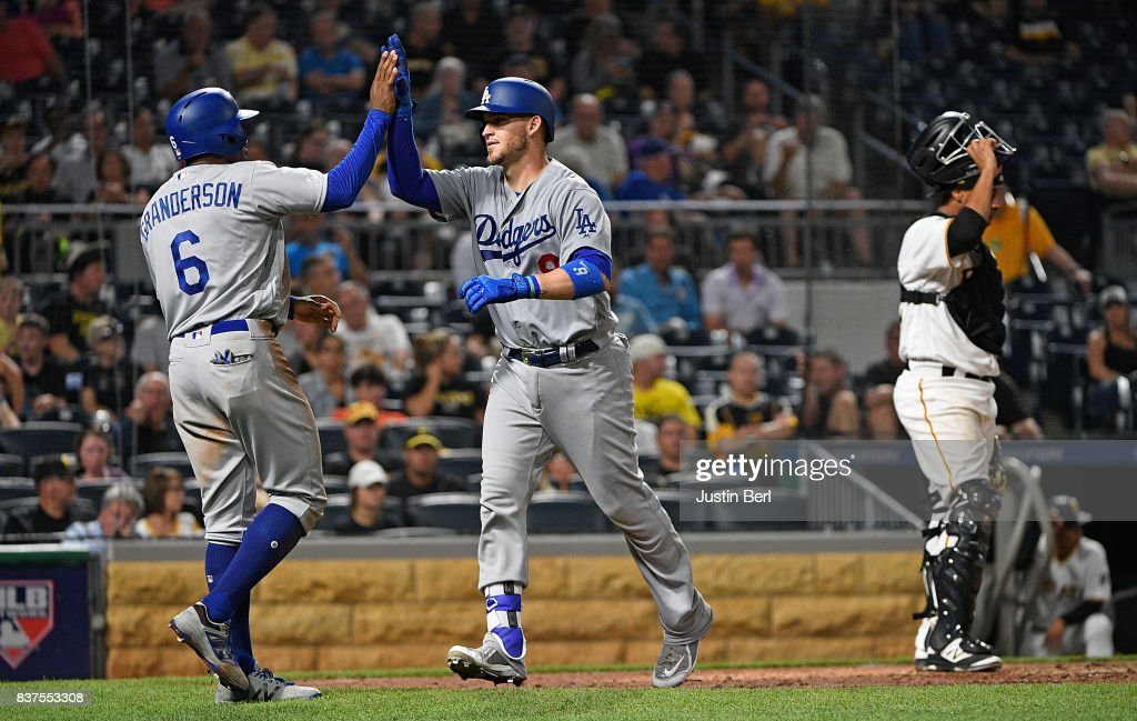 Yasmani Grandal #9 of the Los Angeles Dodgers is greeted by Curtis Granderson #6 after hitting a two run home run in the seventh inning during the game against the Pittsburgh Pirates at PNC Park on August 22, 2017 in Pittsburgh, Pennsylvania.