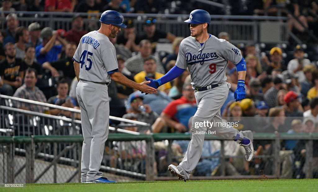 Yasmani Grandal #9 of the Los Angeles Dodgers is greeted by third base coach Chris Woodward #45 as he rounds the bases after hitting a two run home run in the seventh inning during the game against the Pittsburgh Pirates at PNC Park on August 22, 2017 in Pittsburgh, Pennsylvania.