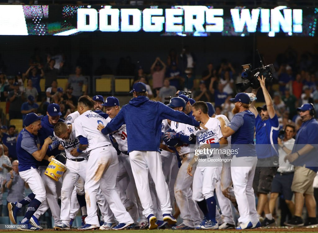 Yasmani Grandal #9 of the Los Angeles Dodgers (third from left) is mobbed by teammates after Grandal hit a two-run walk-off homerun over the right field fence in the tenth inning of the MLB game against the Milwaukee Brewers at Dodger Stadium on August 1, 2018 in Los Angeles, California. The Dodgers defeated the Brewers 6-4.
