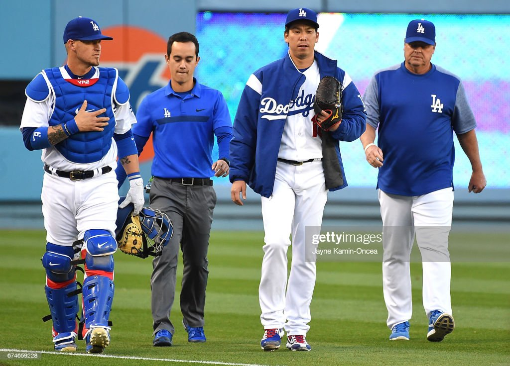 Yasmani Grandal #9 of the Los Angeles Dodgers, Kenta Maeda #18 of the Los Angeles Dodgers, Maeda's translator and pitching coach Rick Honeycutt #40 walk in from the bullpen after warming up for the game against the Philadelphia Phillies at Dodger Stadium on April 28, 2017 in Los Angeles, California.