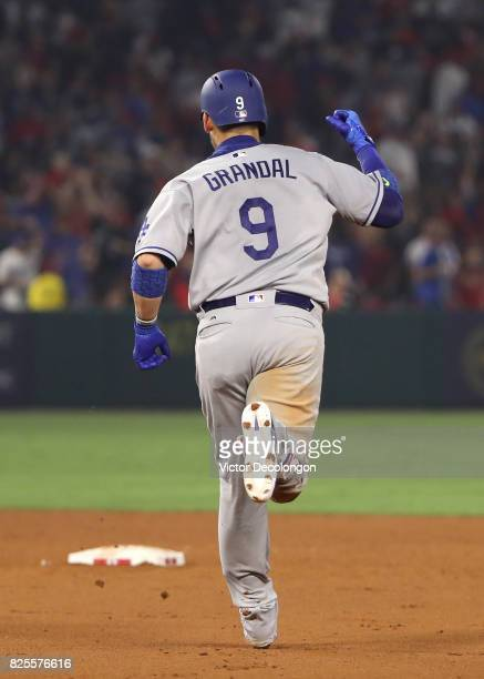 Yasmani Grandal of the Los Angeles Dodgers pumps his fist en route to second base after hitting the gametying homerun in the ninth inning during the...