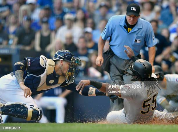 Yasmani Grandal of the Milwaukee Brewers tags out Josh Bell of the Pittsburgh Pirates at home plate in the first inning at Miller Park on June 29...