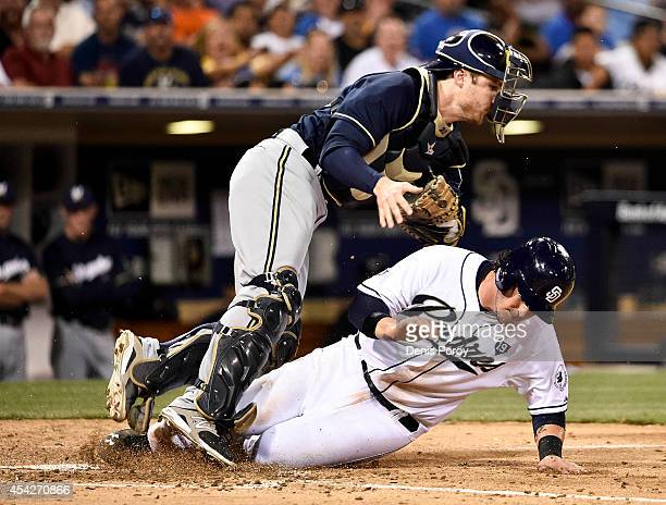 Yasmani Grandal of the San Diego Padres is tagged out at the plate by Jonathan Lucroy of the Milwaukee Brewers during the fifth inning of a baseball...