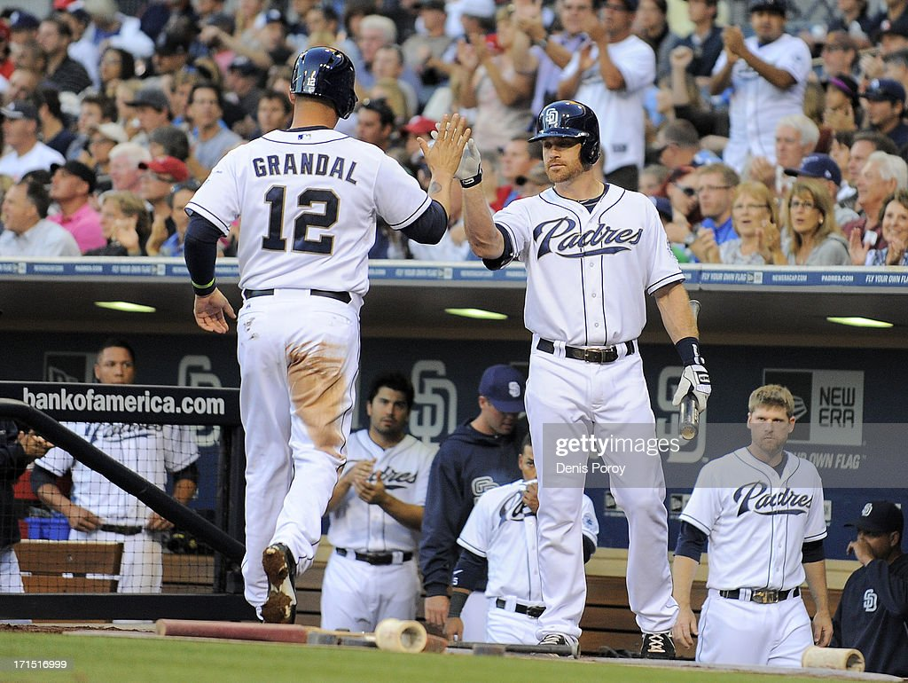 Yasmani Grandal #12 of the San Diego Padres, left, is congratulated by Logan Forsythe #11 after scoring during the second inning of a baseball game against the Philadelphia Phillies at Petco Park on June 25, 2013 in San Diego, California.