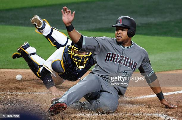 Yasmany Tomas of the Arizona Diamondbacks scores ahead of the tag of Derek Norris of the San Diego Padres during the seventh inning of a baseball...