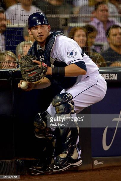 Yasmati Grandal of the San Diego Padres retrieves a wild pitch from the backstop and throws to first base against the Arizona Diamondbacks at Petco...