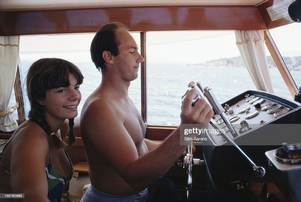 Yasmin Aga Khan and her half-brother, Prince Karim Aga Khan IV, who is at the controls of a yacht, on the waters off the coast of Porto Cervo on the Costa Smeralda, Sardinia, Italy, in August 1968.