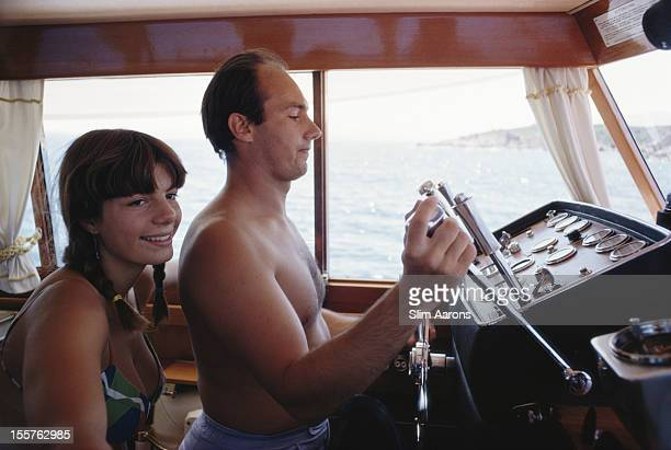 Yasmin Aga Khan and her halfbrother Prince Karim Aga Khan IV who is at the controls of a yacht on the waters off the coast of Porto Cervo on the...