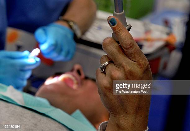 Yasmin Bellavigna of Laurel holds the rinsing suction tube as she was being treated today Bellavigna was the very first person in line for treatment...