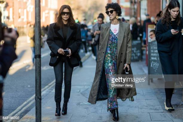 Yasmin Sewell wearing a dress with floral print grey coat and Christine Centenera wearing a black jacket denim jeans outside JW Anderson on day 2 of...