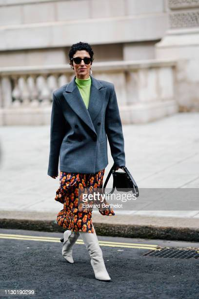 Yasmin Sewell wears a gray blazer jacket an orange floral print skirt white boots a green top earrings sunglasses during London Fashion Week February...