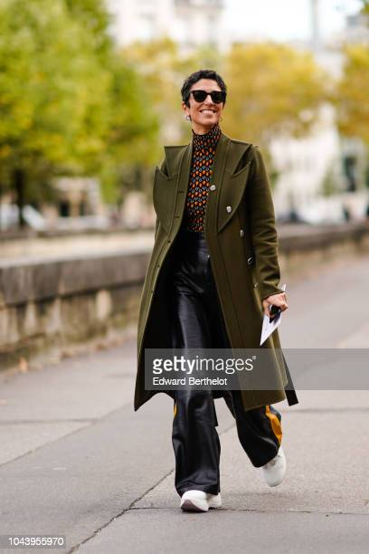 Yasmin Sewell wears a green khaki coat a multicolor turtleneck black leather flare pants white sneakers outside Valentino during Paris Fashion Week...