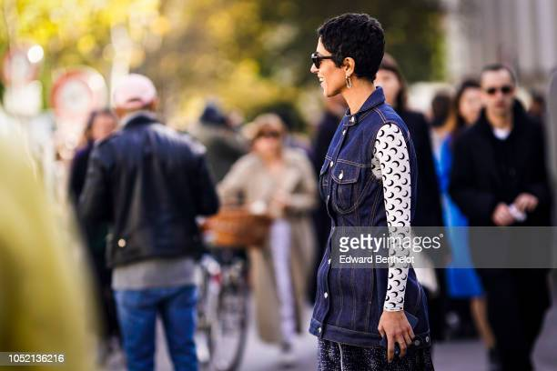 Yasmin Sewell wears a sleeveless blue denim jacket a white top with printed black items sunglasses a blue skirt outside Haider Ackermann during Paris...
