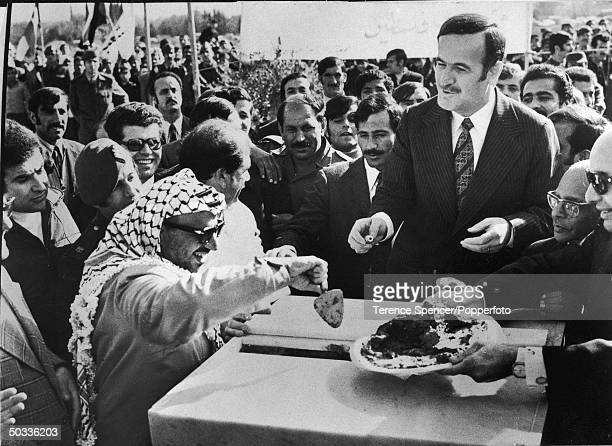 PLO leader Yasser Arafat w Syrian Pres Hafez Assad appearing convivial at crowdframed event