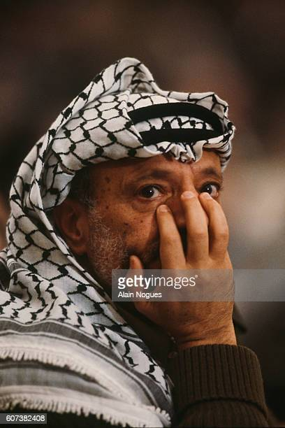 Yasser Arafat leader of the Palestine Liberation Organization puts his hand over his face during the 16th session of the Palestinian National Council...