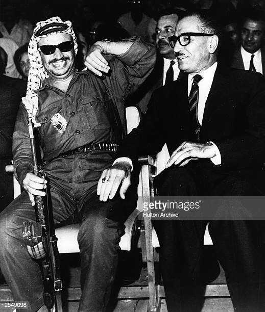 Yasser Arafat leader of the PLO holding a Russianmade machine gun laughs while sitting next to Jordanian premier Abdul Mon'er Rifai during the...