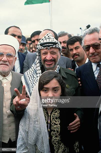Yasser Arafat, leader of the PLO, poses with a young girl during a meeting of PLO leaders.