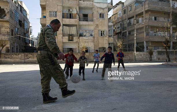 Yasser Nabhan plays football with children in Syria's northern city of Aleppo Saif alDawla district on March 11 2016 Syria's war has transformed...