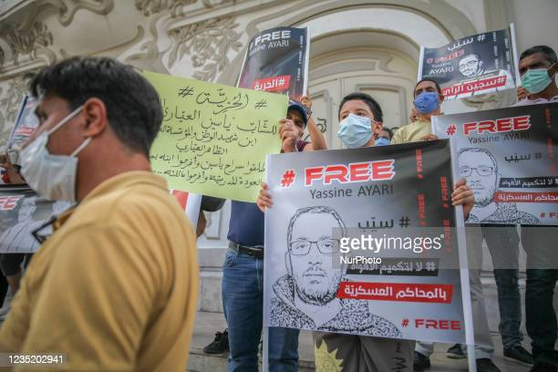 Yassine Ayariss son holds a placard that reads in english Free Yassine Ayari and another one that reads in Arabic no to muzzling the mouths by...