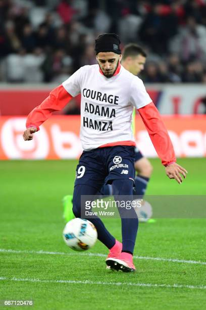 Yassine Benzia of Lille warms up in a tshirt supporting injured team mates Hamza Mendyl and Adama Soumaoro before the French Ligue 1 match between...