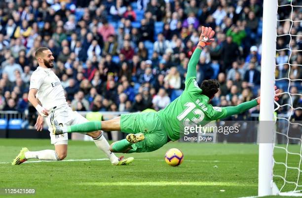 Yassine Bounou of Girona dives to save the ball from Karim Benzema of Real Madrid during the La Liga match between Real Madrid CF and Girona FC at...