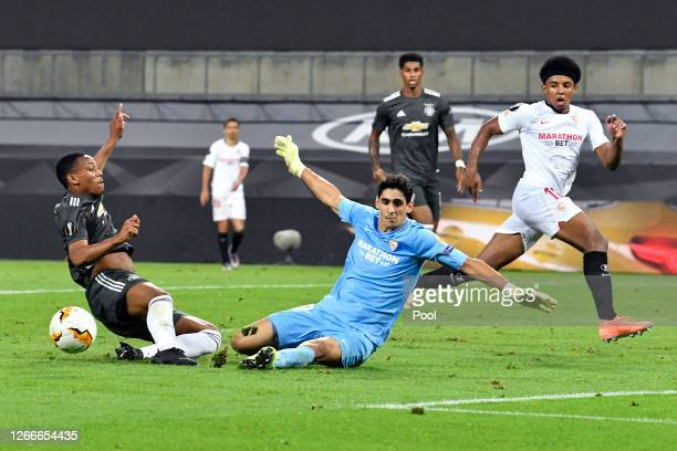Yassine Bounou of Sevilla FC makes a save from Anthony Martial of Manchester United during the UEFA Europa League Semi Final between Sevilla and...