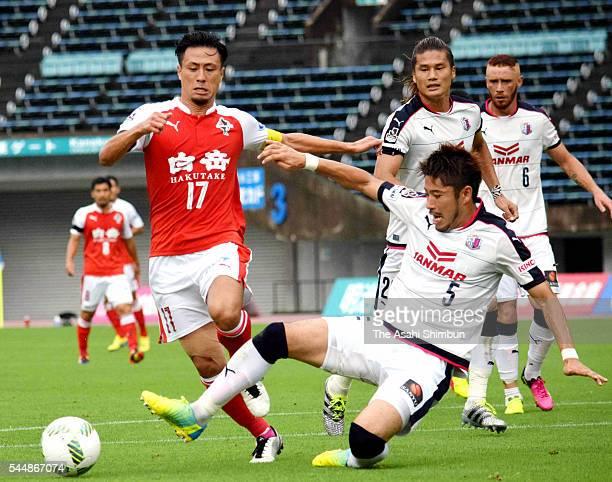 Yasuaki Okamoto of Roasso Kumamoto is tackled by Yusuke Tanaka of Cerezo Osaka during the J.League second division match between Roasso Kumamoto and...