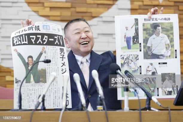 Yasuhiko Abe, who coached golfer Hideki Matsuyama during his Tohoku Fukushi University years, holds special editions of newspapers featuring...