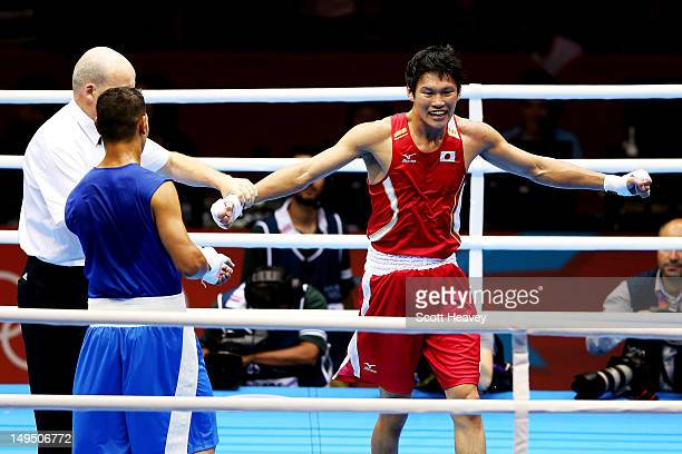 Yasuhiro Suzuki of Japan celebrates his victory over Mehdi Khalsi of Morocco during their Men's Welter Boxing bout on day 2 of the London 2012...