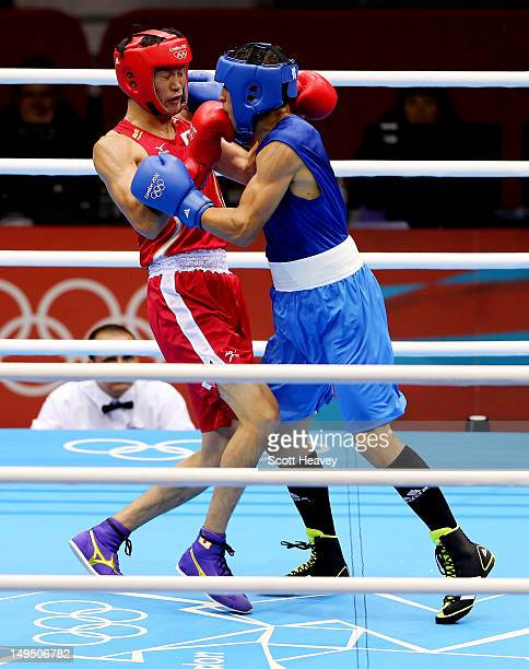 Yasuhiro Suzuki of Japan in action with Mehdi Khalsi of Morocco during their Men's Welter Boxing bout on day 2 of the London 2012 Olympic Games at...