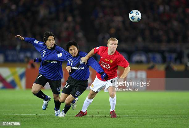 Yasuhito Endo and Hideo Hashimoto of Gamba Osaka battle for the ball with Wayne Rooney of Manchester United
